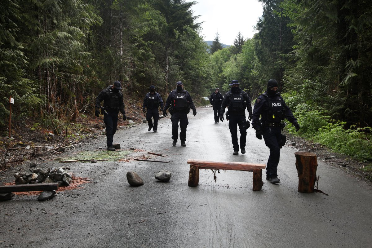 Police move obstacles out of the road at an anti-logging blockade in Caycuse, B.C. on Tuesday, May 18, 2021.