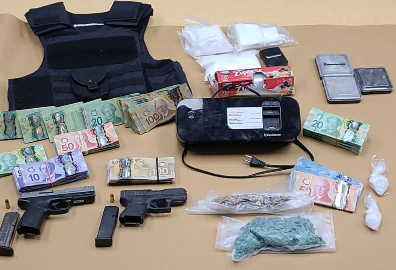 Police say officers seized nearly $200,000 in suspected drugs as well as two loaded guns and about $50,000 in cash.