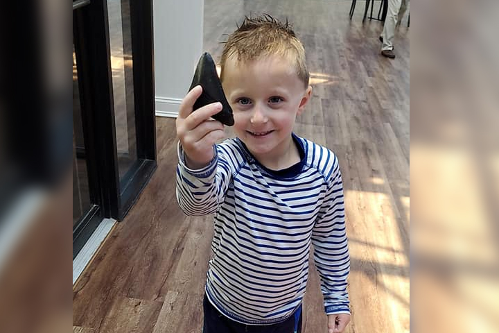 Brayden Drew, 5, shows off a megalodon shark tooth that he found in Myrtle Beach, S.C., on May 20, 2021.