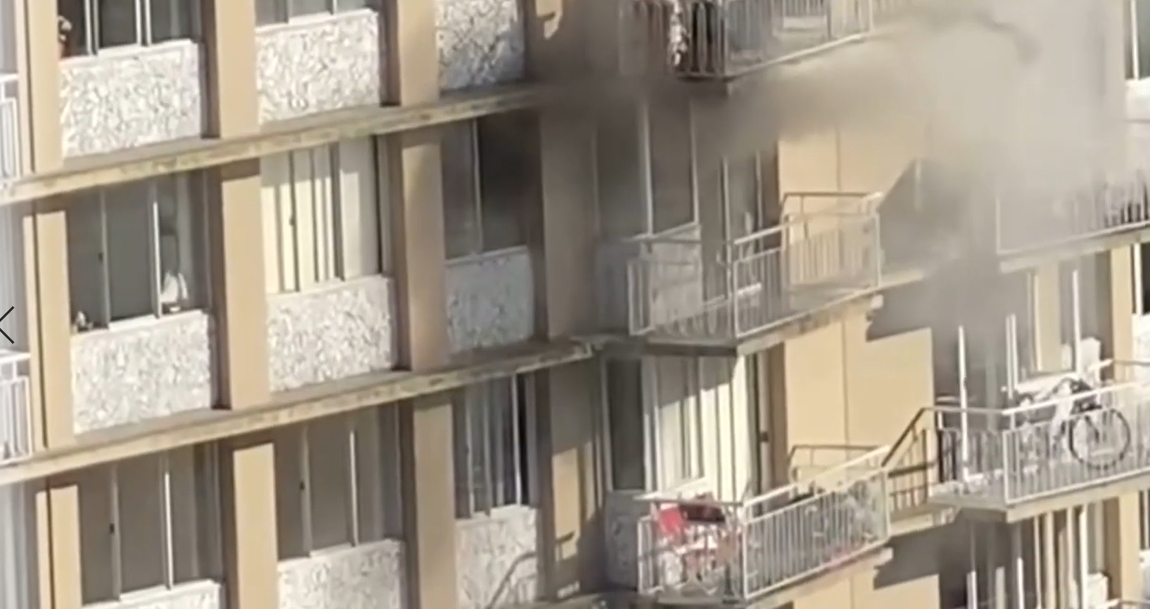 Smoke pours from an 11th-floor unit in a West End apartment Saturday evening.