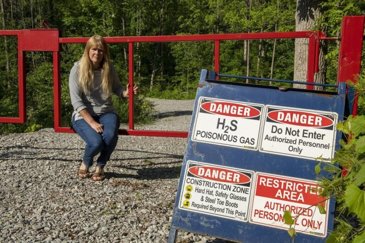 Paula Jongerden sits by a sign next to her property in Norfolk County on Thursday, June 10, 2021.