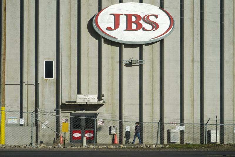 FILE - In this Oct. 12, 2020 file photo, a worker heads into the JBS meatpacking plant in Greeley, Colo. A weekend ransomware attack on the world's largest meat company is disrupting production around the world just weeks after a similar incident shut down a U.S. oil pipeline. The White House confirms that Brazil-based meat processor JBS SA notified the U.S. government Sunday, May 30, 2021, of a ransom demand from a criminal organization likely based in Russia.