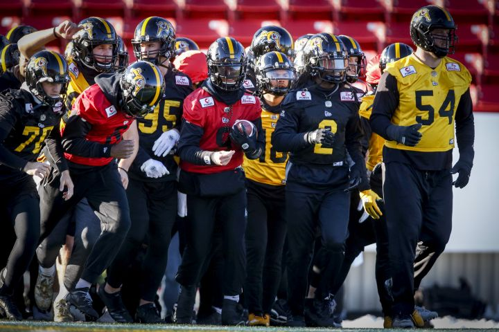 Hamilton Tiger-Cats quarterback Dane Evans, centre, runs onto the field with teammates during practice for Sunday's CFL Grey Cup football game in Calgary, Friday, Nov. 22, 2019.