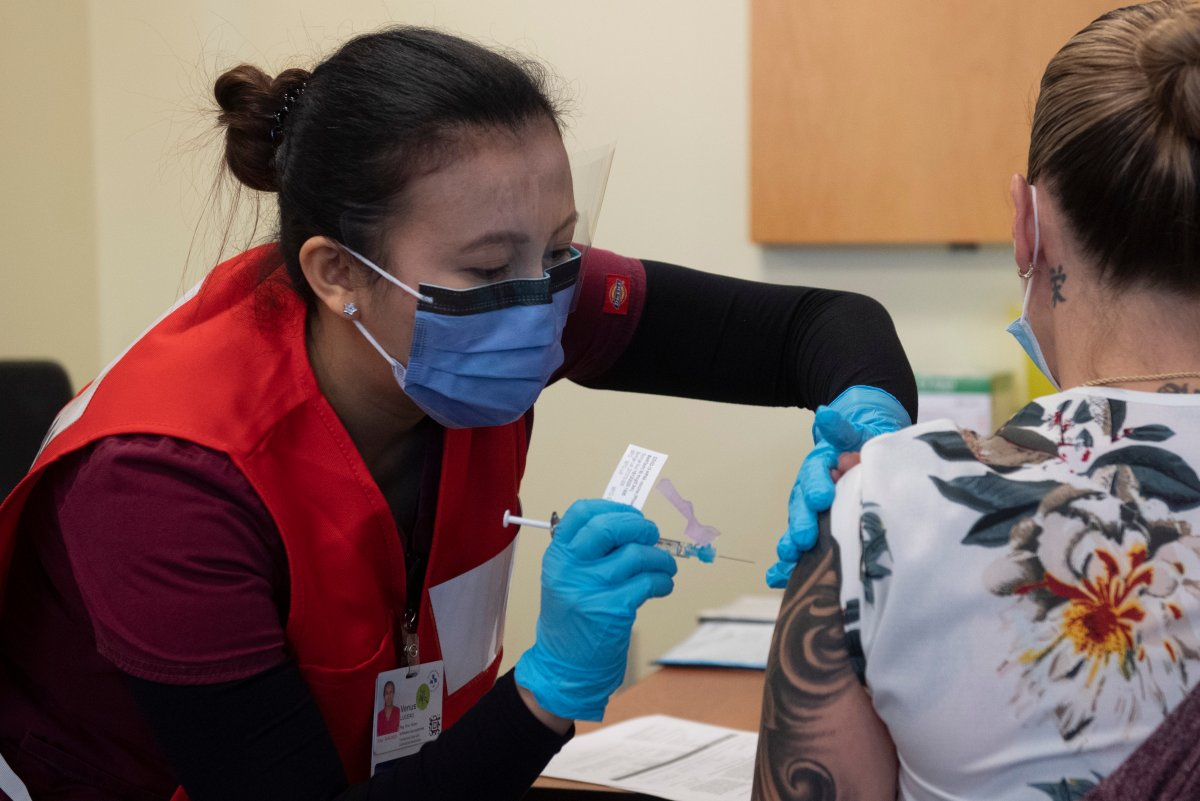 Nurse Venus Lucero administers the first Pfizer-BioNTech COVID-19 vaccine at the Ottawa Hospital to Jo-Anne Miner at a vaccination clinic, Tuesday, Dec. 15, 2020 in Ottawa.