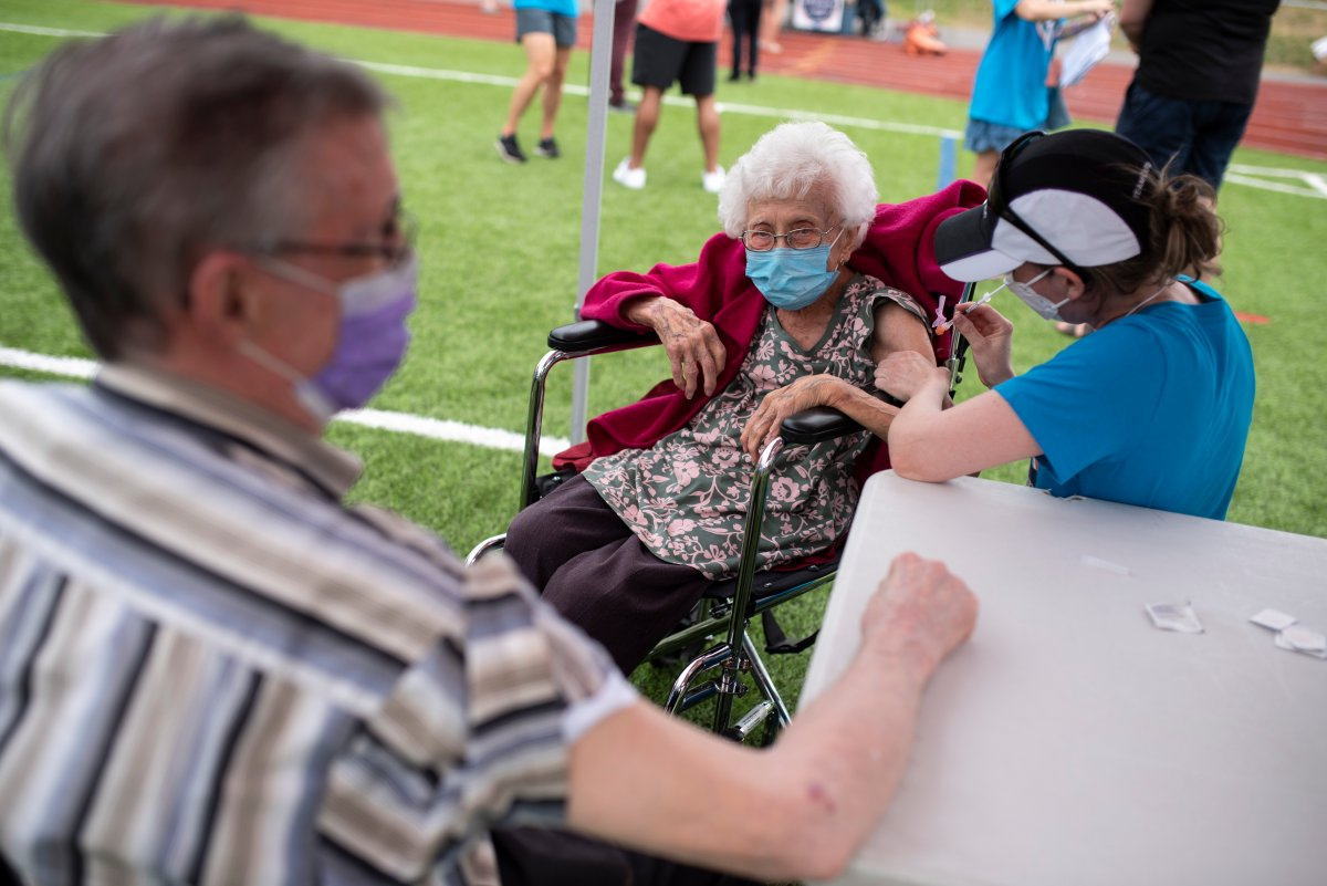 """Dr. Katie Baldwin delivers a COVID-19 vaccine to Jeanne St. Onge, 101, as her husband Denis, 92, waits for his dose, at  an outdoor, pop-up vaccination clinic nicknamed """"Jabapalooza"""" on the soccer field at Immaculata High School in Ottawa, on Saturday, June 5, 2021."""