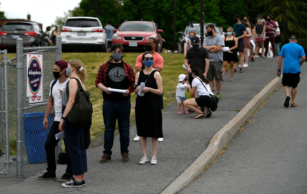 """People line up for their appointments at an outdoor, pop-up COVID-19 vaccination clinic nicknamed """"Jabapalooza"""" on the soccer field at Immaculata High School in Ottawa, on Saturday, June 5, 2021."""
