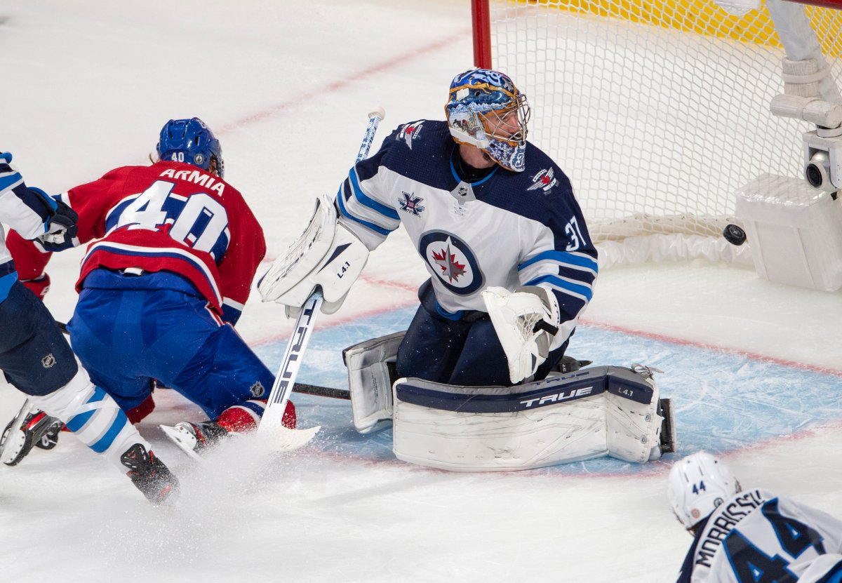 Montreal Canadiens' Joel Armia (40) scores a shorthanded goal on Winnipeg Jets goaltender Connor Hellebuyck (37) as Jets' Josh Morrissey (44) looks on during second period NHL Stanley Cup playoff hockey action in Montreal, Sunday, June 6, 2021.