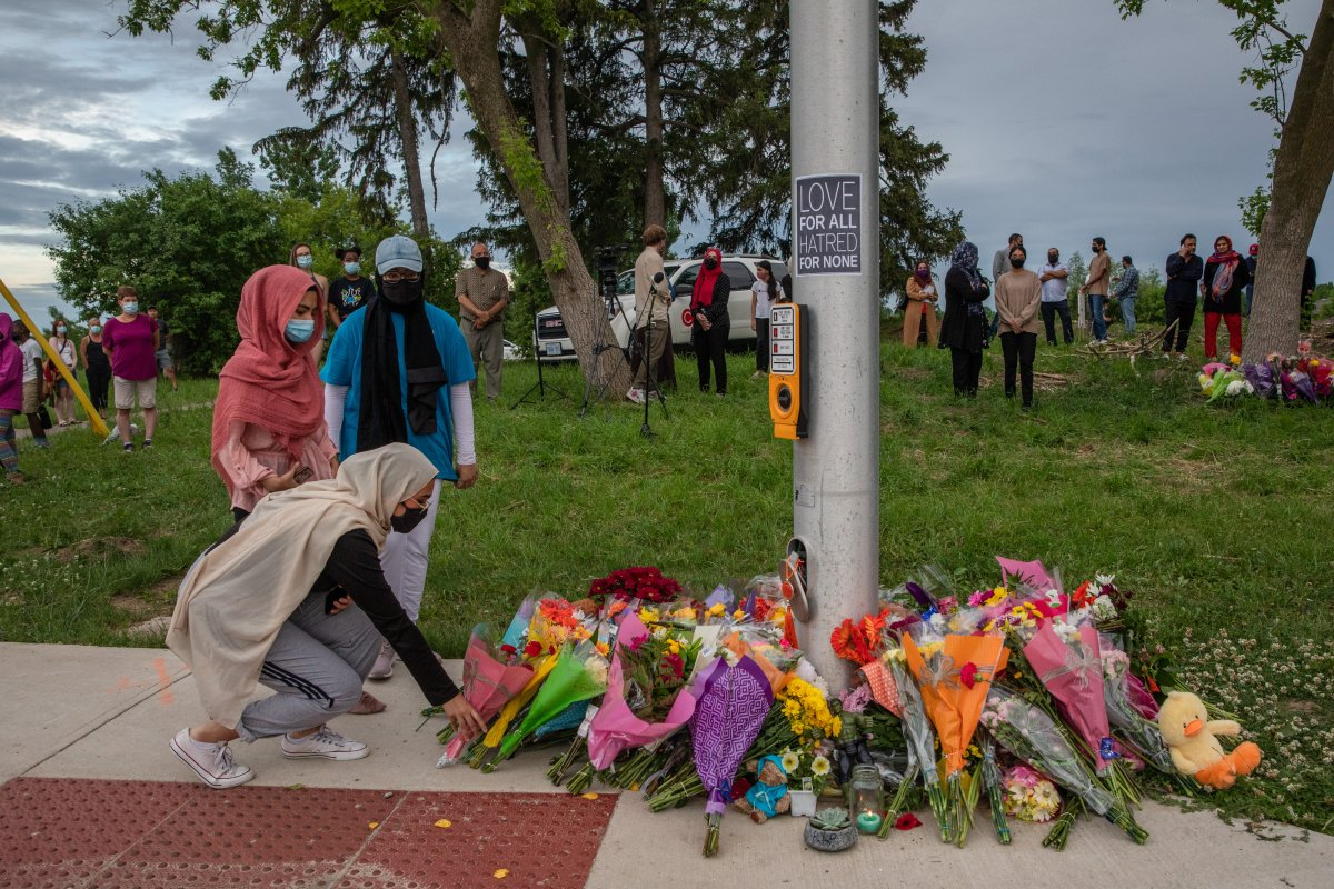 Mourners leave flowers at the site where a family of five was hit by a driver, in London, Ont., Monday, June 7, 2021. Four of the members of the family died and one is in critical condition.