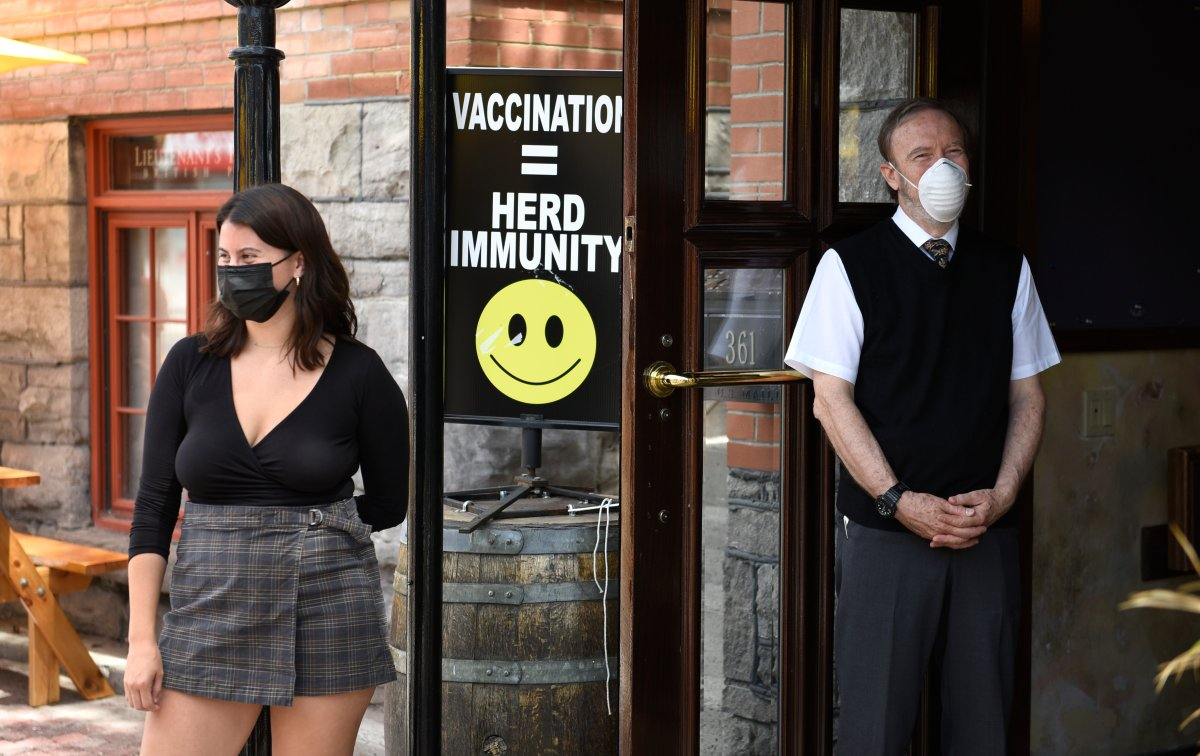 A sign encouraging vaccination is seen at the doors of a pub as staff watch patrons arrive, in Ottawa on the first day of Ontario's first phase of re-opening amidst the third wave of the COVID-19 pandemic, on Friday, June 11, 2021.