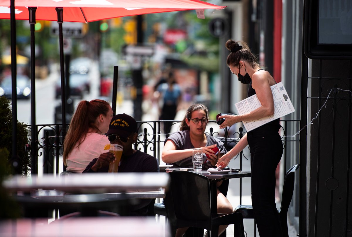 Patrons settle up with a server on a pub's outdoor patio in Ottawa on the first day of Ontario's first phase of reopening amidst the third wave of the COVID-19 pandemic, on Friday, June 11, 2021.