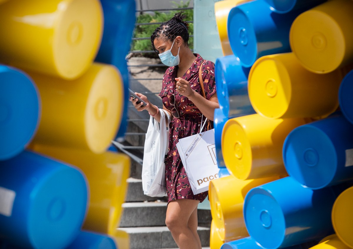 A woman wears a face mask as she walks by an art installation in Montreal, Sunday, June 13, 2021, as the COVID-19 pandemic continues in Canada and around the world.