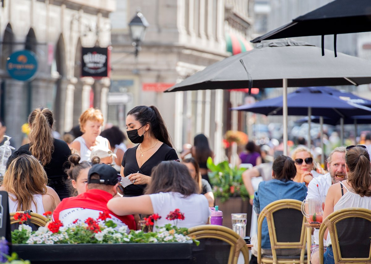 People sit on a terrace in Old Montreal, Sunday, June 13, 2021, as the COVID-19 pandemic continues in Canada and around the world.