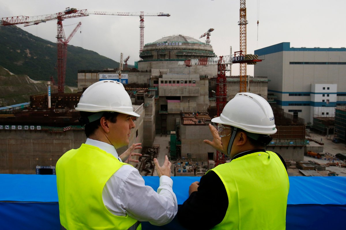 """FILE - In this Oct. 17, 2013, file photo, then British Chancellor of the Exchequer George Osborne, left, chats with Taishan Nuclear Power Joint Venture Co. Ltd. General Manager Guo Liming as he inspects a nuclear reactor under construction at the nuclear power plant in Taishan, southeastern China's Guangdong province. The French joint operator of the Chinese nuclear plant near Hong Kong said Monday it is dealing with a """"performance issue"""" but is currently operating within safety limits, following a report of a potential radioactive leak. (AP Photo/Bobby Yip, Pool, File)."""