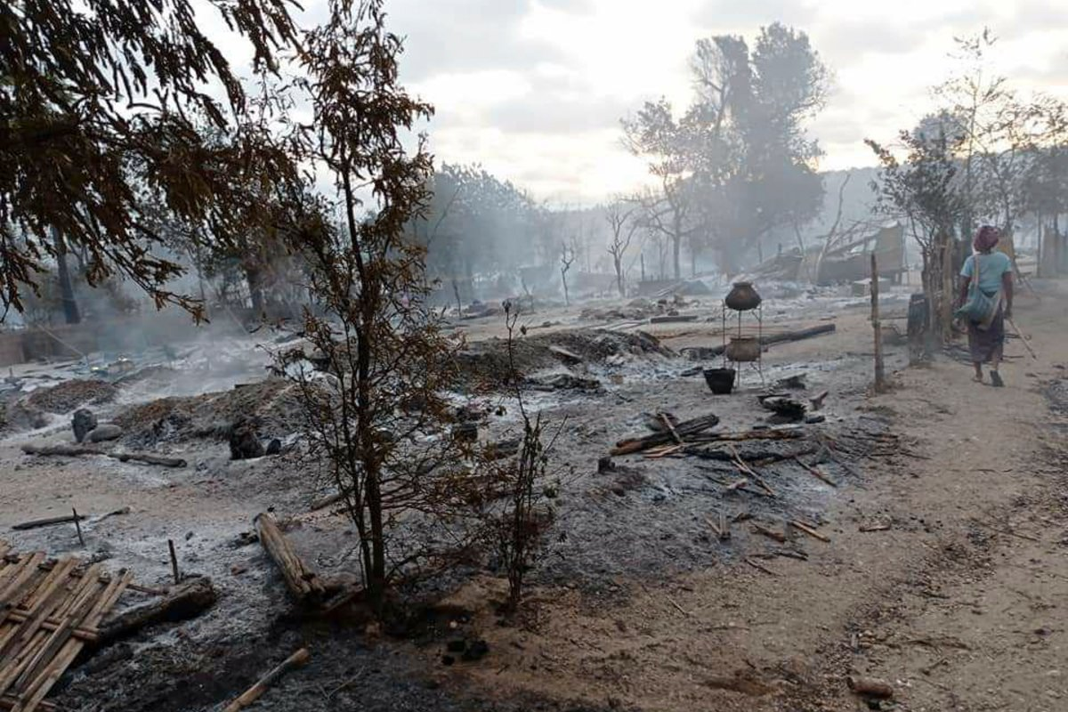 A resident walks past smoldering houses in the Kinma village, Pauk township, Magwe division, central Myanmar, Wednesday, June 16, 2021. Residents said people are missing after military troops burned the village the night before. (AP Photo).