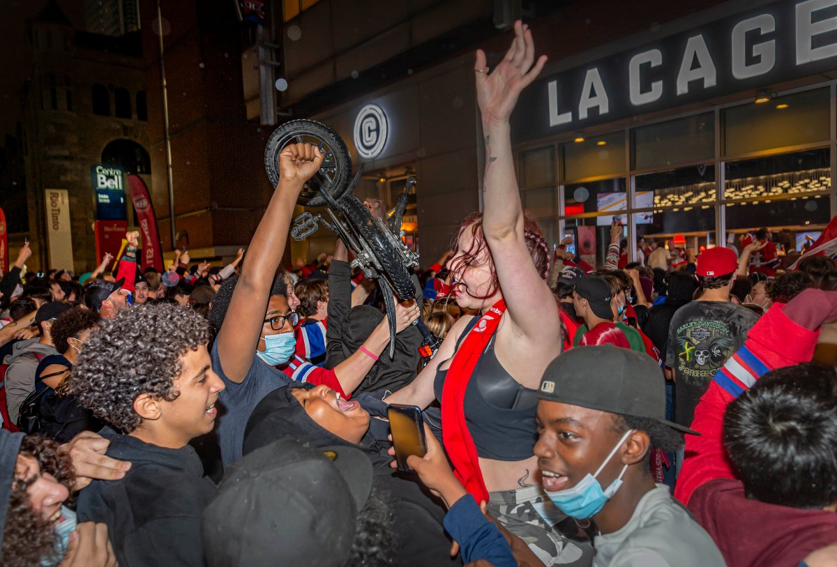 Montreal Canadiens fans celebrate their team's overtime victory over the Vegas Golden Knights in Game 3 of the NHL Stanley Cup semifinal outside of the Bell Centre in Montreal on Friday, June 18, 2021 in Montreal.