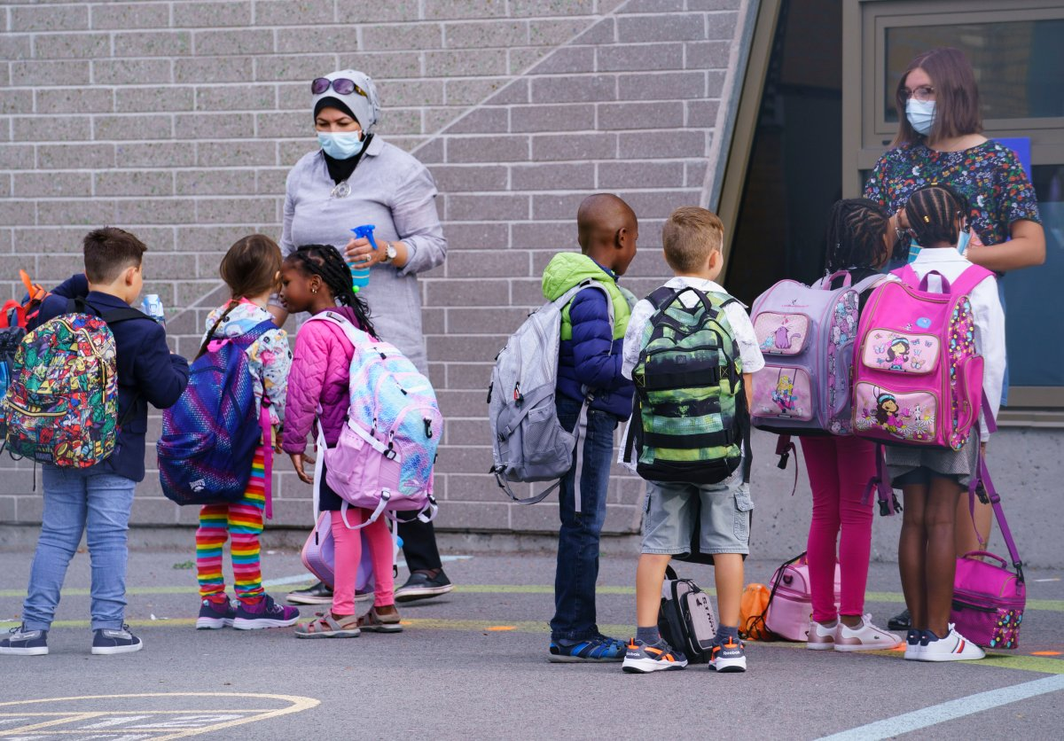 Teachers greet their students in the school yard at the Philippe-Labarre Elementary School in Montreal, on Thursday, August 27, 2020. Thousands of Quebec students return to class in the shadow of the COVID-19 pandemic.