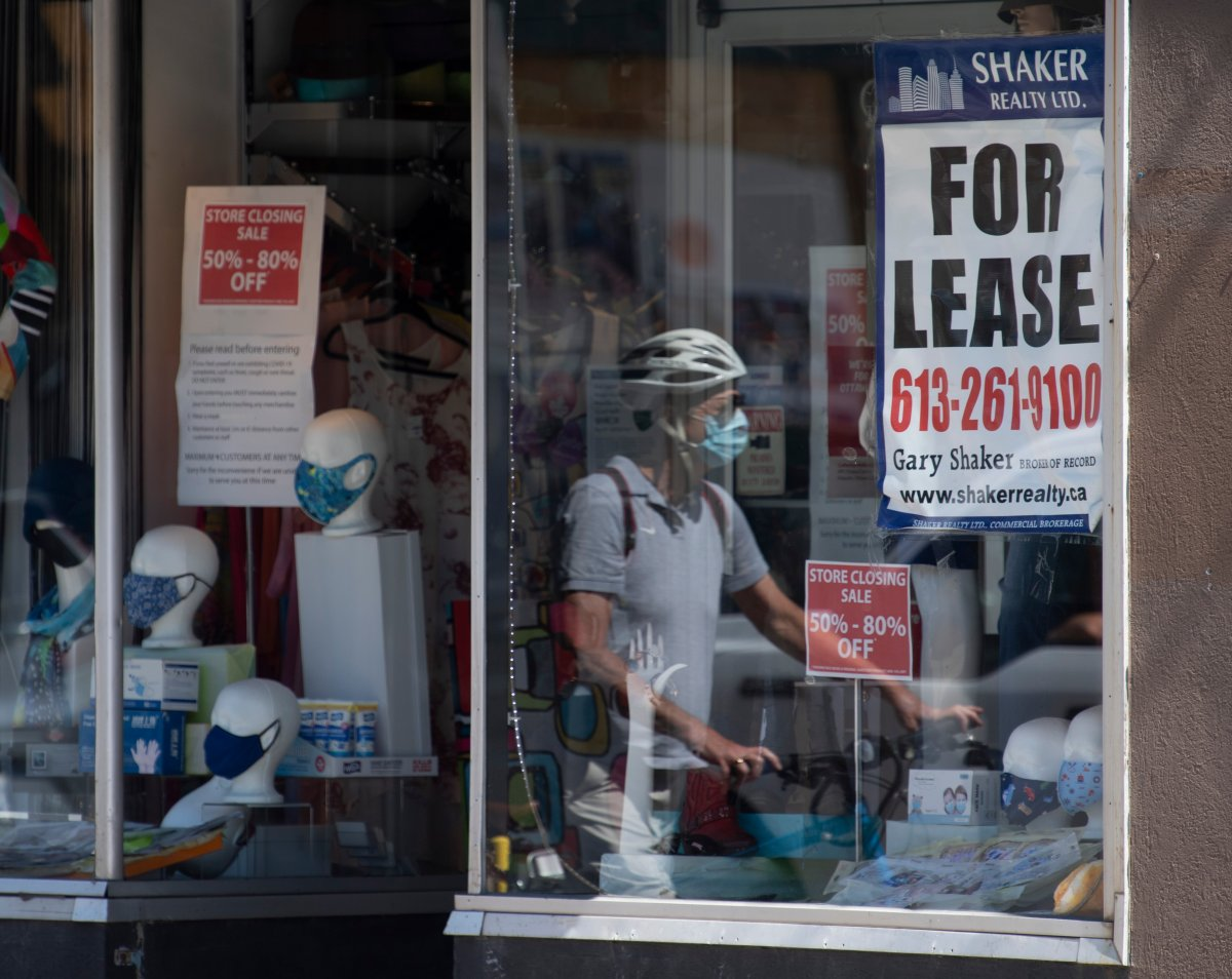A lease sign hangs in the window as a cyclist walks past a commercial store Monday August 31, 2020 in Ottawa.