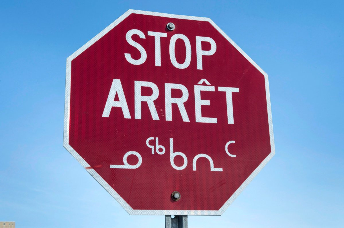 A stop sign in English, French and Inuit in Iqaluit, Nunavut.