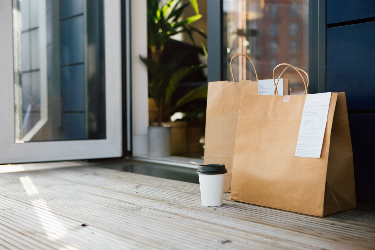 Takeaway meal packed in brown paper bag delivered to the front door of a residential building.