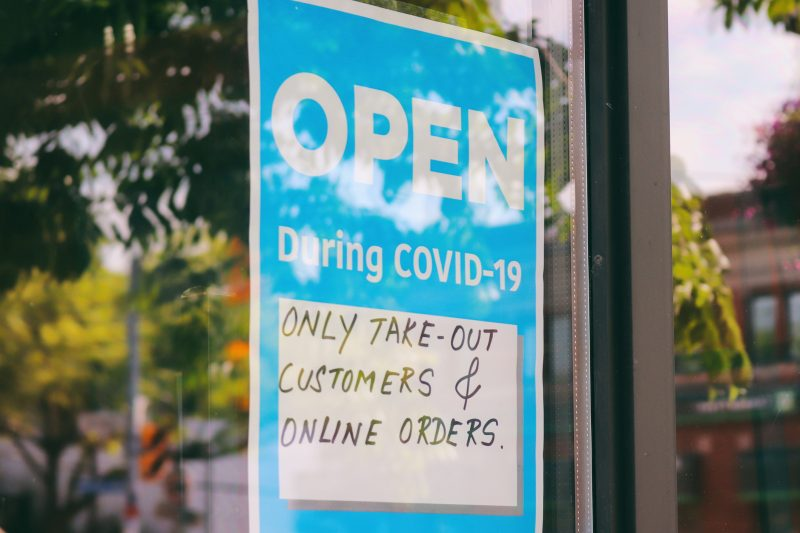 A sign indicates a restaurant is open during the COVID-19 pandemic but only for takeout or online orders.