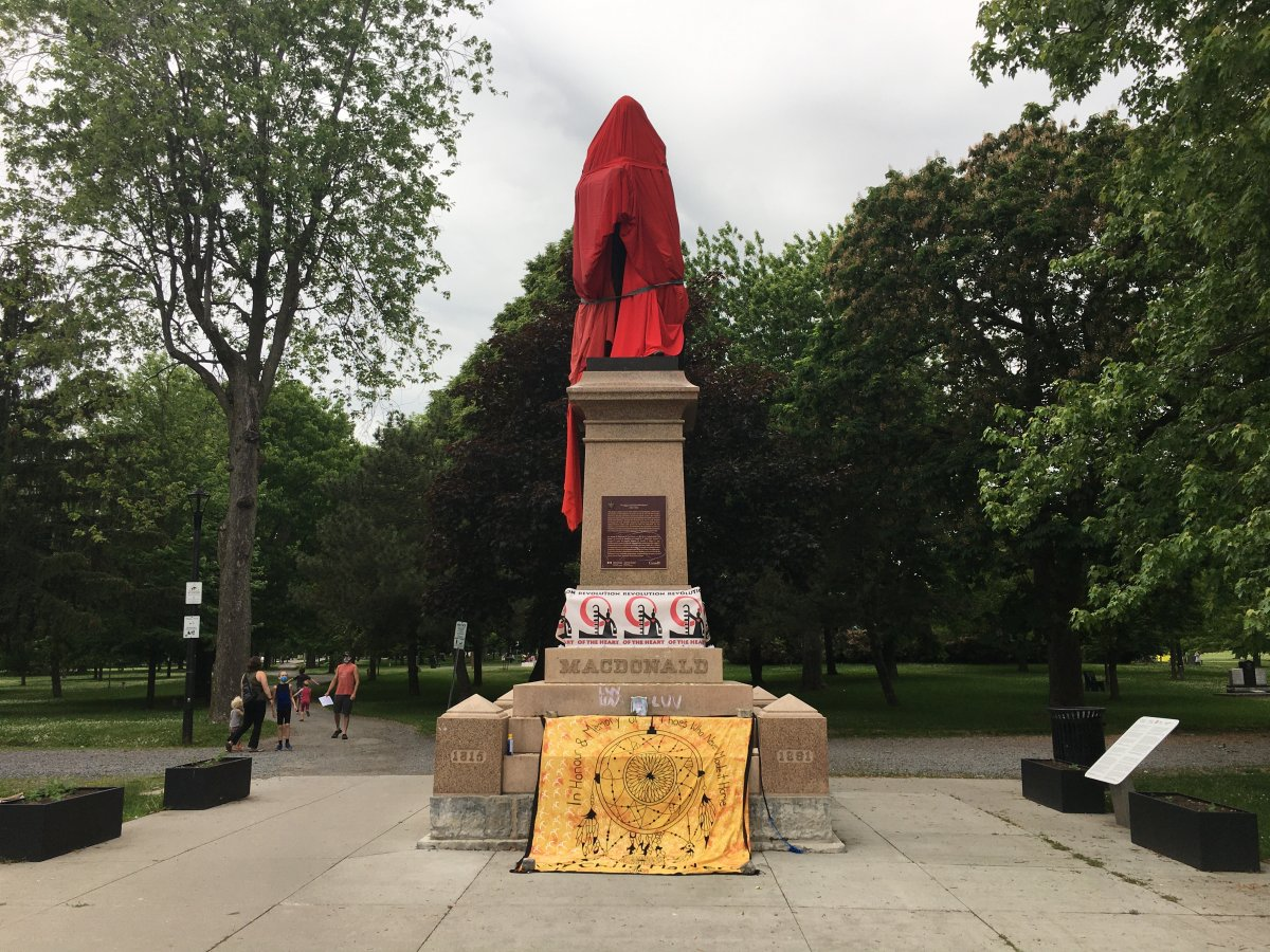 A statue of Sir John A. Macdonald in Kingston's City Park has been covered by a red tarp by a group wanting for the statue to be taken down.