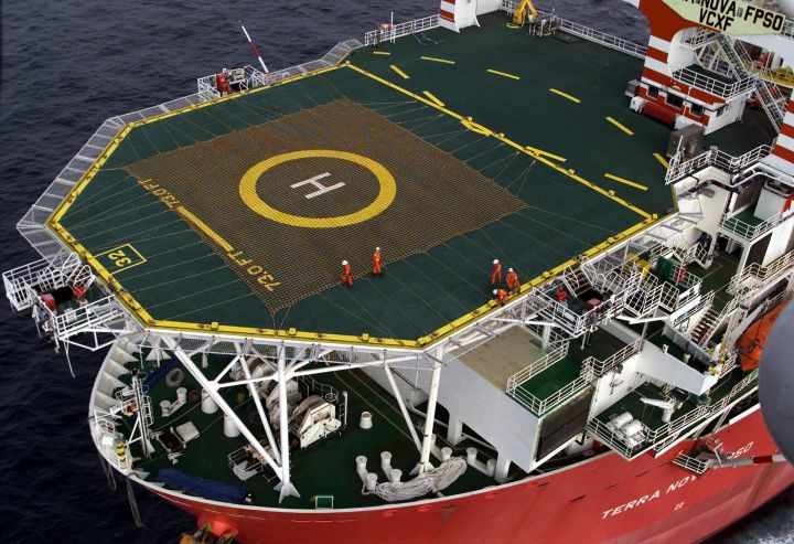 Workers stand on the helicopter landing pad on Terra Nova FPSO, a massive floating production, storage and offloading vessel used in the oil and gas industry, as it heads along the Newfoundland coast on Friday, Aug. 3, 2001. The $2.9 billion vessel, which stands 14 stories tall, will be used off the Newfoundland coast in the province's second major offshore project.