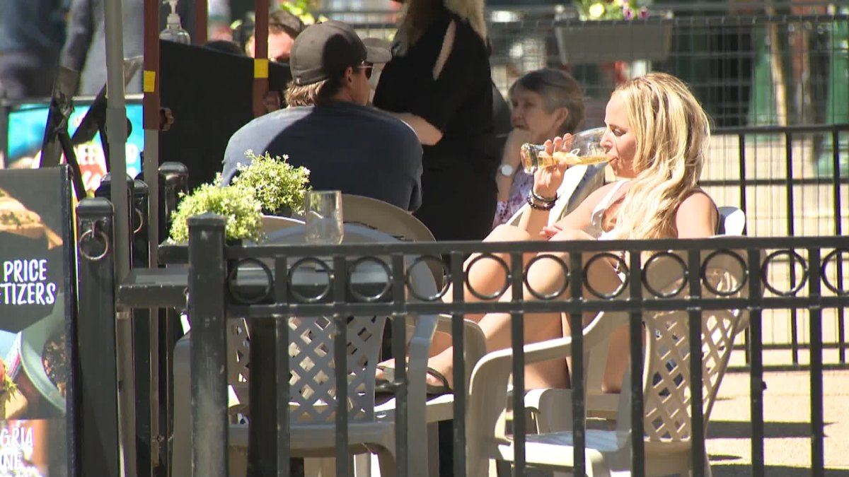 A woman enjoys a beverage on a Calgary patio on Tuesday, June 1, 2021.