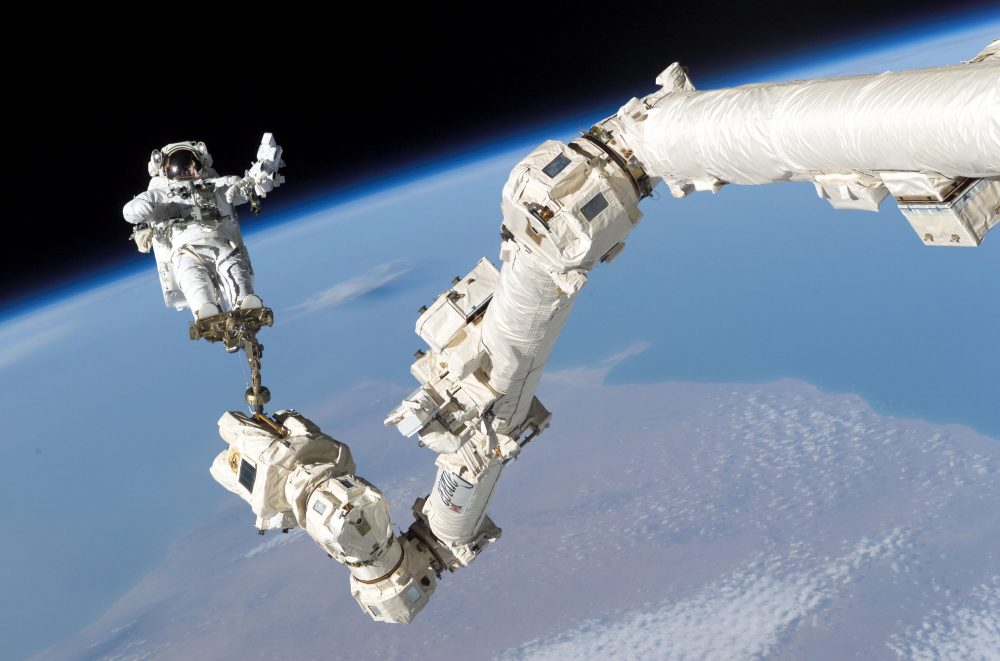 This Aug. 3, 2005 file photo shows an astronaut anchored to the Canadarm2 robotic arm on the International Space Station.