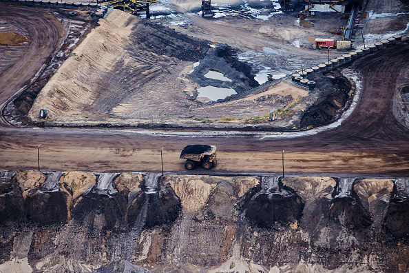 A heavy hauler truck drives through the Syncrude Canada Ltd. Aurora North mine in this aerial photograph taken above the Athabasca oil sands near Fort McMurray, Alberta, Canada, on Monday, Sept. 10, 2018.