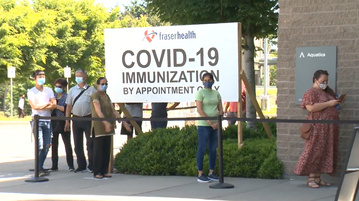 People line up to be immunized against COVID-19 at the Guildford Rec Centre on Sunday.