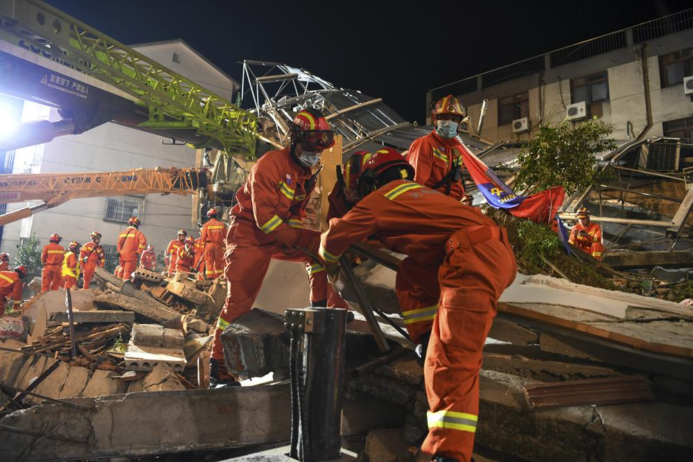 In this photo released by Xinhua News Agency, rescuers prepare equipment as they search for survivors at a collapsed hotel in Suzhou in eastern China's Jiangsu Province on Monday, July 12, 2021. The hotel building collapsed Monday afternoon. (Li Bo/Xinhua via AP).