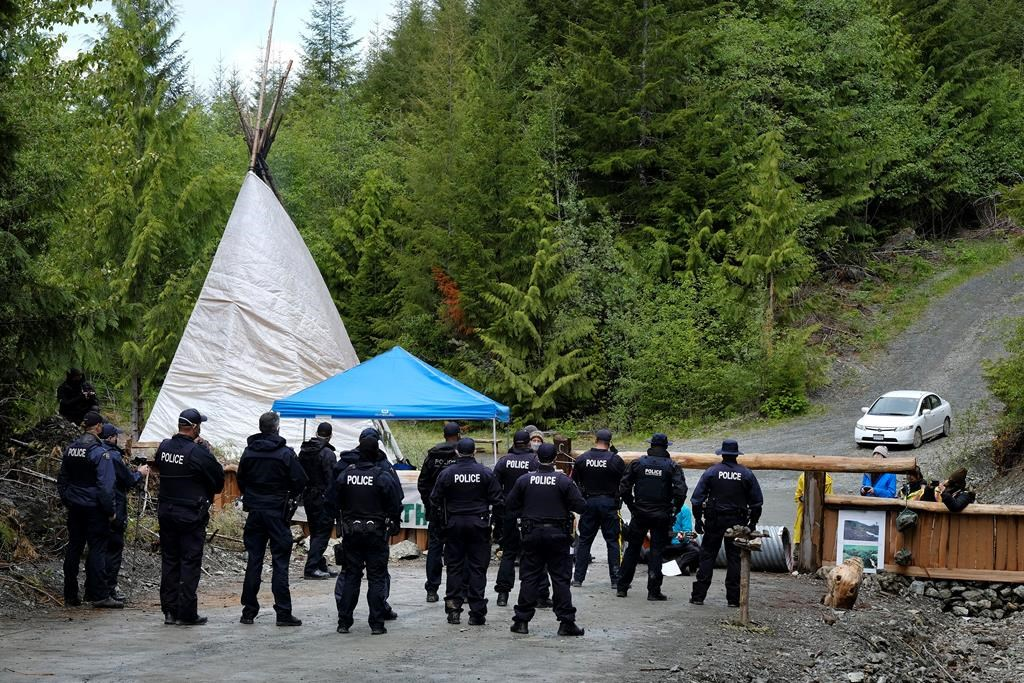RCMP officers approach an anti-logging blockade in Caycuse, B.C. on Tuesday, May 18, 2021. THE CANADIAN PRESS/Jen Osborne.