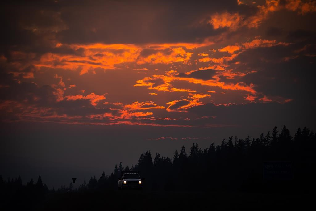 Smoke particles from wildfires enhance the colour of a sunset as a motorist travels on Highway 97C near Logan Lake, B.C., on Thursday, July 15, 2021. Above average temperatures for many parts of B.C. aren't expected to ease soon and Environment Canada says there is no hint of showers until at least the weekend for some regions of southern B.C. hit hard by wildfires. THE CANADIAN PRESS/Darryl Dyck.