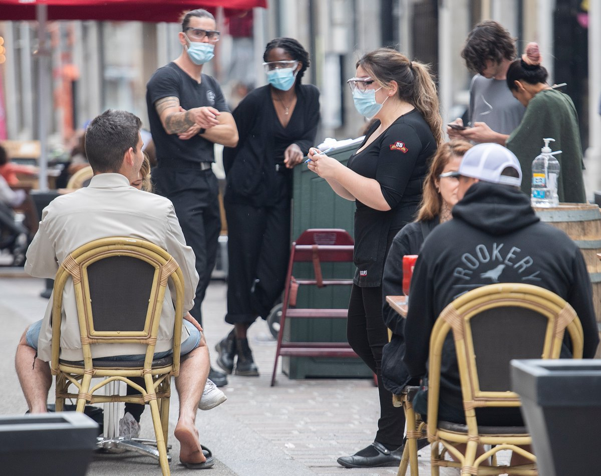 A server wears a face mask as she takes an order on a terrace at a restaurant in Old Montreal, Sunday, May 30, 2021, as the COVID-19 pandemic continues in Canada and around the world.