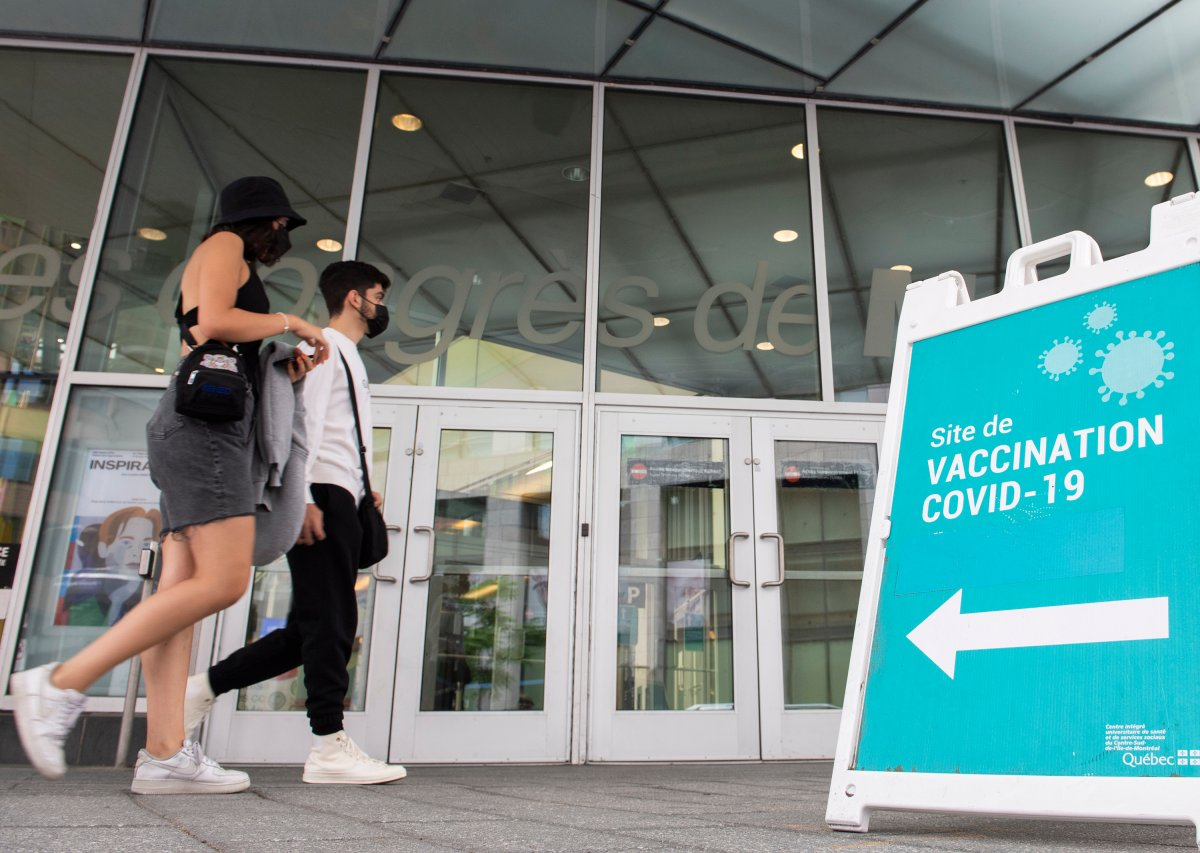 People wear face masks as they walk by a sign at a COVID-19 vaccination site in Montreal, Sunday, July 4, 2021.