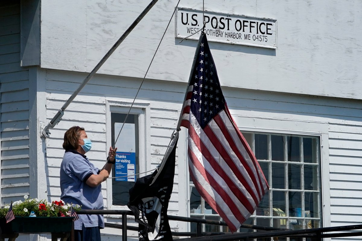 An employee raises the American flag outside a branch of the U.S. Post Office, Wednesday, July 7, 2021, in West Boothbay Harbor, Maine.