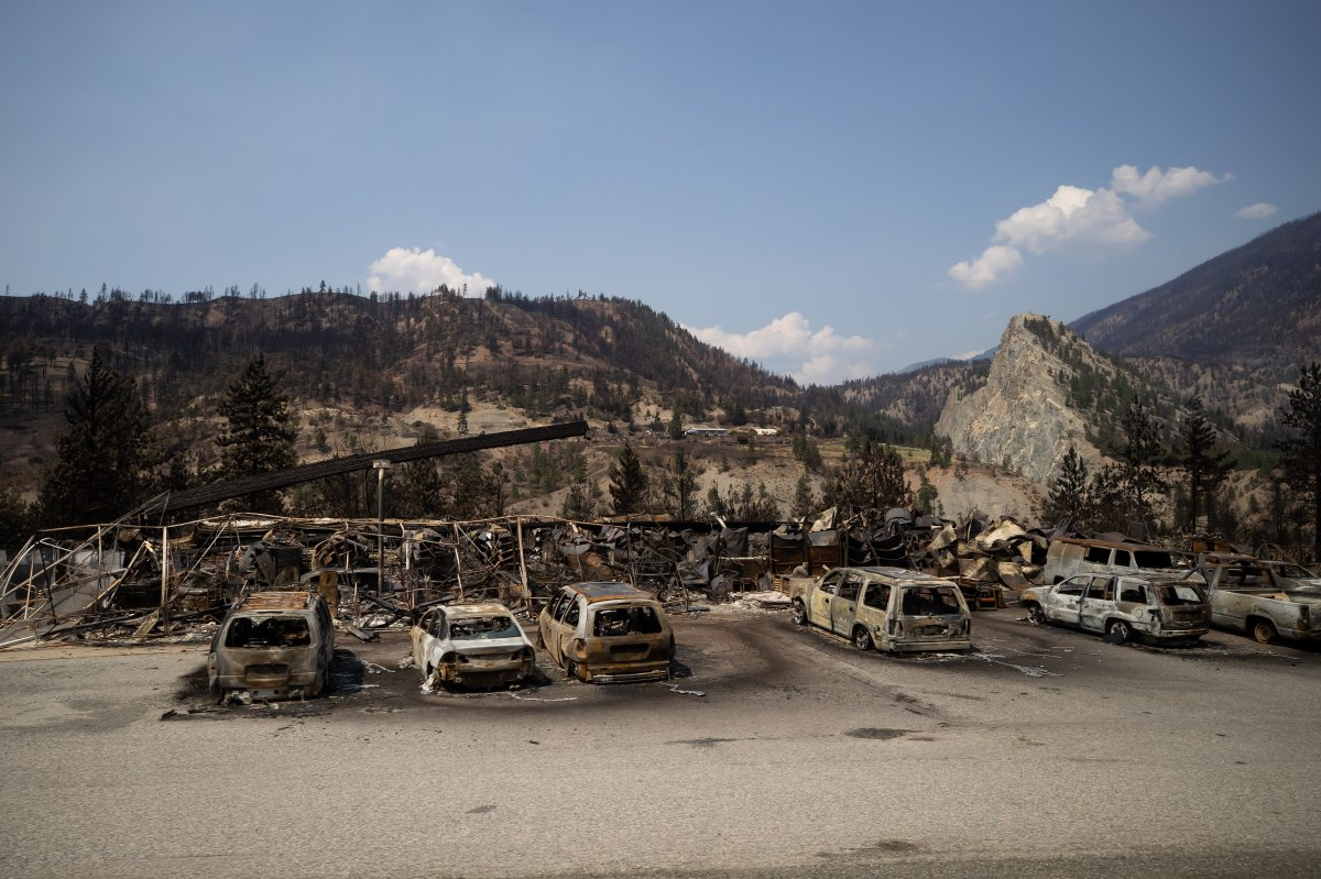 Cars destroyed by wildfire and a damaged structure are seen along the Trans-Canada Highway near Lytton, B.C., on Friday, July 9, 2021.