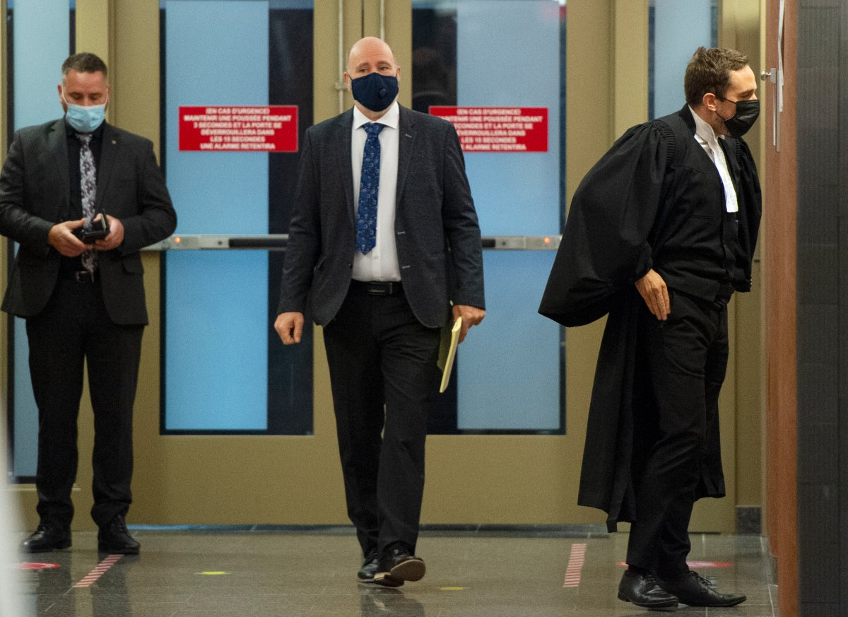 Montreal police officer Roger Frechette, centre, leaves the courtroom during a break in his sexual assault trial Tuesday, July 13, 2021 in Montreal.