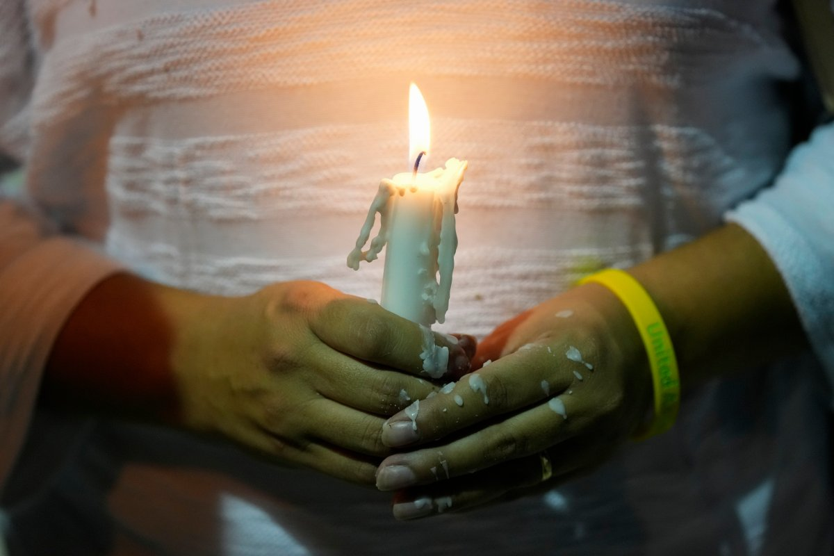 Dislamy Pelayo holds a candle during a multi-faith vigil for victims of the Champlain Towers South condo building collapse, near the site where the building once stood, Thursday, July 15, 2021, in Surfside, Fla.