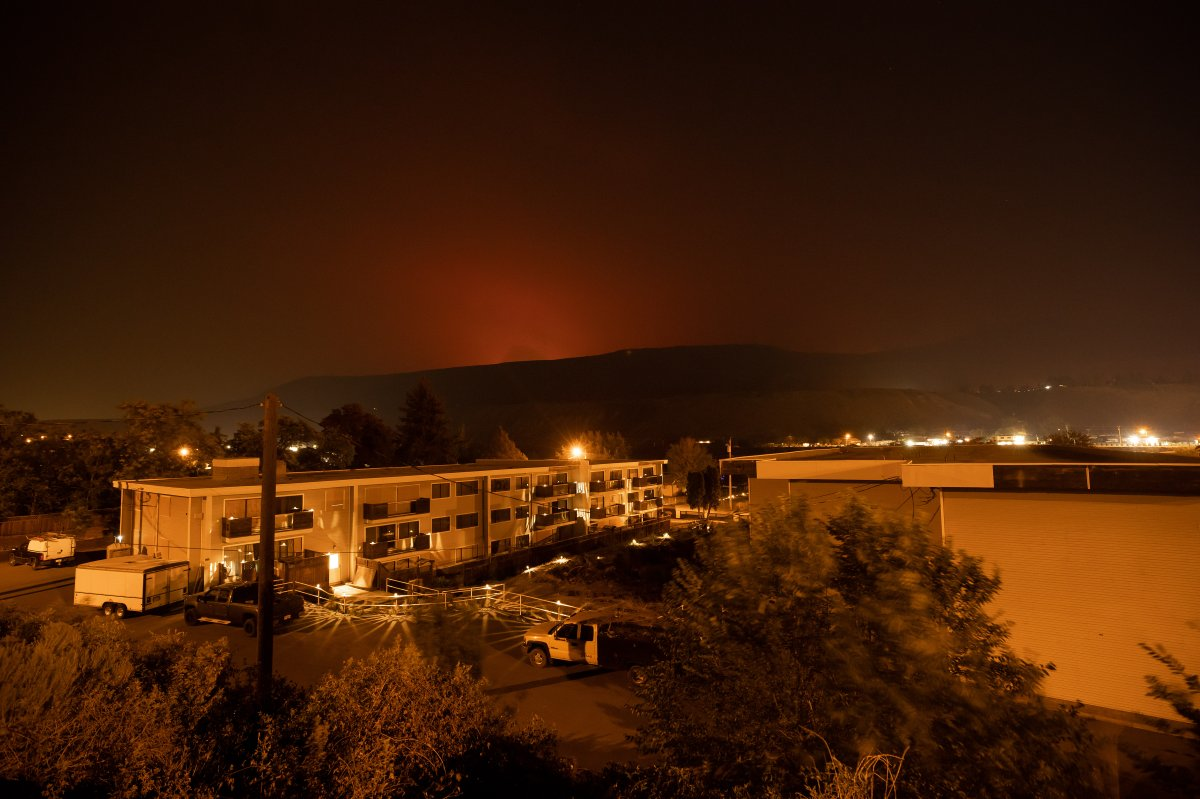 The sky glows orange as the Tremont Creek wildfire burns on a mountain in the distance above Ashcroft, B.C., on Thursday, July 15, 2021.