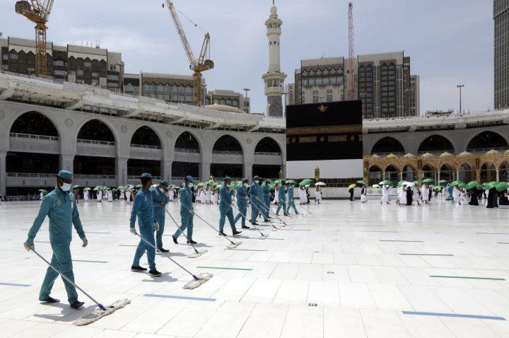 Arbeiter desinfizieren das Gelände, während muslimische Pilger einen Tag vor der jährlichen Hadsch-Pilgerfahrt, Samstag, 17. Juli 2021, die Kaaba, das kubische Gebäude der Großen Moschee, umrunden.
