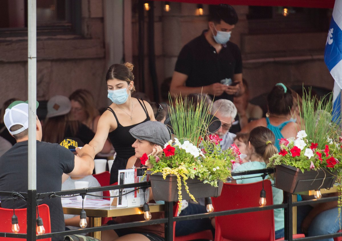 A server wears a face mask as she tends to customers in Old Montreal, Sunday, July 18 2021, as the COVID-19 pandemic continues in Canada and around the world.