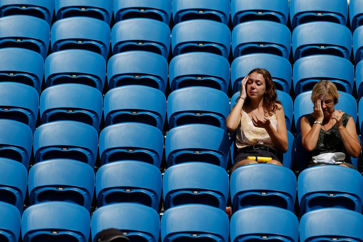 Fans apply sunscreen as they wait for a match in their third round match between Argentina's Diego Schwartzman and Serbia's Dusan Lajovic at the Australian Open tennis championship in Melbourne, Australia, Friday, Jan. 24, 2020.