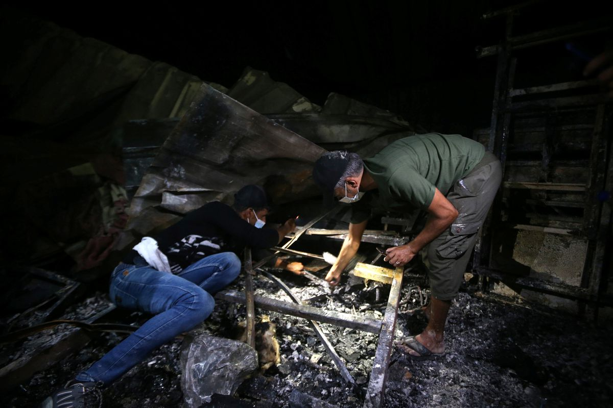 People inspect the damage at the site where a fire broke out at al-Hussain coronavirus hospital, in Nassiriya, Iraq, July 13, 2021.