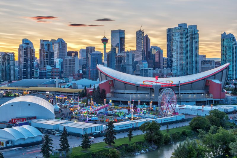 Sunset over Calgary skyline with the annual Stampede event at the Saddledome grounds.