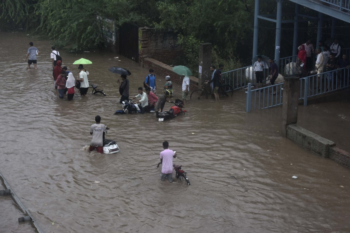 Commuters wade through a waterlogged road due to heavy rains, near Narsingh pur, on July 19, 2021 in New Delhi, India.