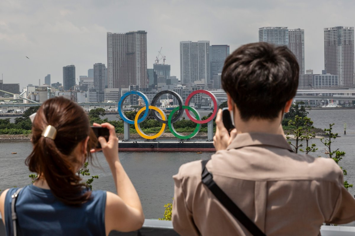 People take pictures of Olympics rings on July 28, 2021 in Tokyo, Japan. Fans have been barred from most Olympic events due to the Covid-19 pandemic, which also caused the Games' yearlong postponement.