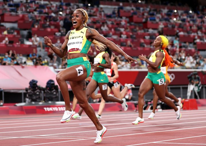 TOKYO, JAPAN - JULY 31: Elaine Thompson-Herah of Team Jamaica celebrates as she crosses the finish line to win the gold medal in the Women's 100m Final on day eight of the Tokyo 2020 Olympic Games at Olympic Stadium on July 31, 2021 in Tokyo, Japan.