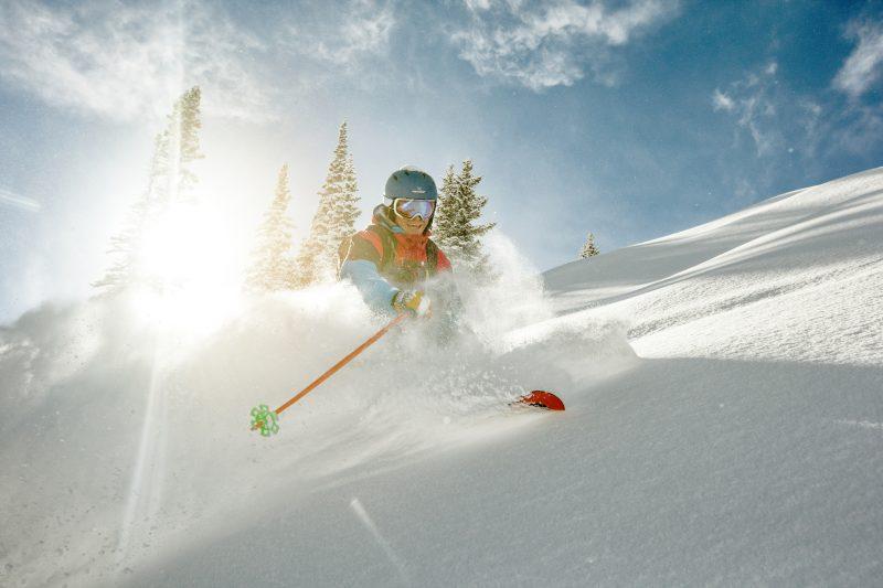 Skier takig a turn in deep powder on a sunny day.