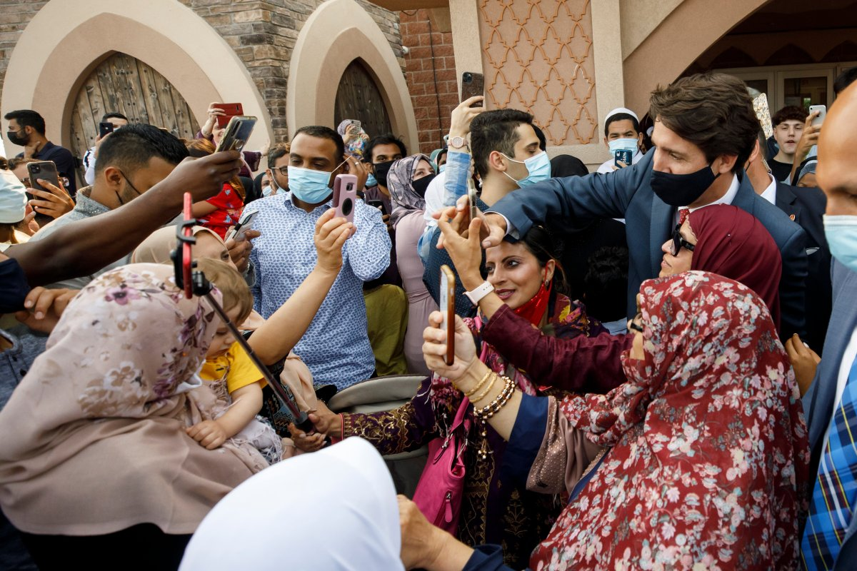 Canada's Prime Minister Justin Trudeau takes selfies with community members at the Hamilton Mountain Mosque after speaking to the congregation to recognize Eid al-Adha in Hamilton, Ont., Tuesday, July 20, 2021.THE CANADIAN PRESS/Cole Burston.